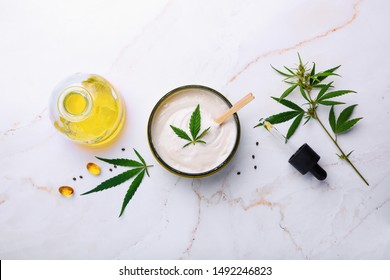 Jar of hemp white lotion. Cannabis cream with marijuana leaf - cannabis concept. Flat lay, top view.
