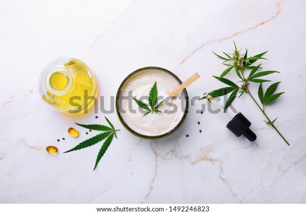 Jar of hemp white lotion. Cannabis cream with marijuana leaf - cannabis concept. Flat lay, top view.
