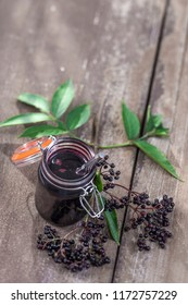 jar of homemade elderberry confiture and fresh fruits
