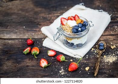 Jar of homemade granola with fresh natural homemade organic yogurt  and berries on dark wood background from top view, Health food from yogurt concept