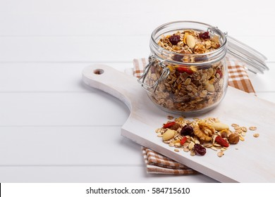 Jar of homemade muesli with nuts, berries, dried fruits,milk and honey on white background.Healthy breakfast. Top view