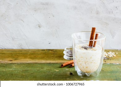 Jar of homemade overnight oats or bircher muesli with cinnamon and honey on old wooden table, selective focus. Concrete wall background. Clean eating, detox, dieting, vegetarian food concept