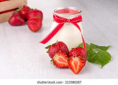 Jar with homemade yogurt and strawberries on white woods