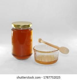 A jar of honey and its honey dipper