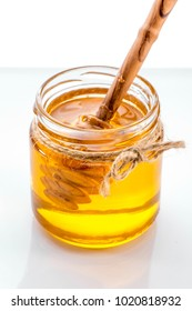 jar of honey with honey dipper  inside close-up on white background