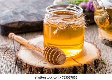 jar of honey with honey dipper on  wooden slice close-up  with teapot and flowers