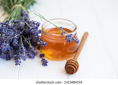 Jar with honey and fresh lavender flowers on a white wooden table