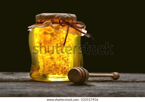 jar of honey with honeycomb with wooden dipper on wooden table