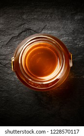 A jar of honey, shot from above on a black background with copy space