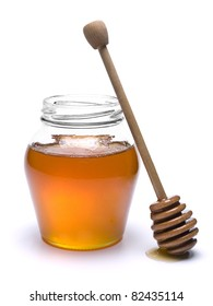 Jar of honey with a wooden drizzler a side. Isolated on white background.