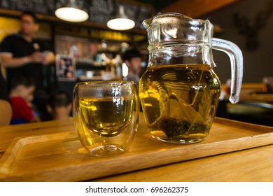 jar of hot tea on wooden tray in coffee shop