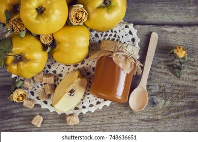 jar of jam and quinces with leaves on wooden rustic background