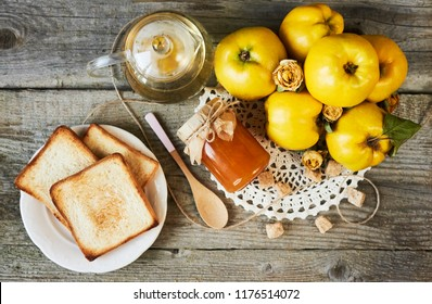 jar of jam with spoon and quinces with leaves on wooden background