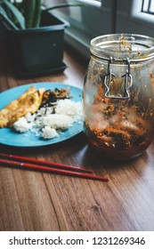 A jar of kimchi on a wooden table next to a blue plate of rice and omelette and a resting pair of red chopsticks