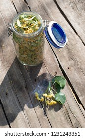 Jar with Linden blossom on wooden table. Sunny day