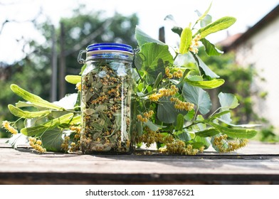 Jar with Linden blossom. Wooden table in the garden. Linden blossom bench