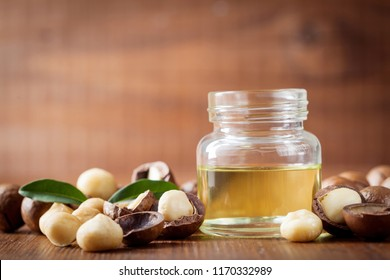 Jar with macadamia oil and heap of nuts on wooden rustic table.
