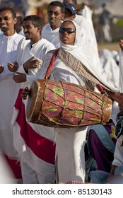 JAR MADA, ADDIS ABABA -  JAN 18: Christian Orthodox devotees playing a traditional drum at the Timket Festival.  January 18, 2009 in Jar Mada, Addis Ababa, Ethiopia