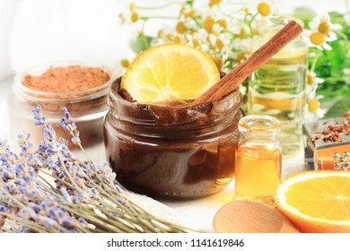 Jar of melted chocolate face mask with aroma orange oil and lavender blossom. Homemade cosmetic products source of vitamins for skincare and beauty treatment.