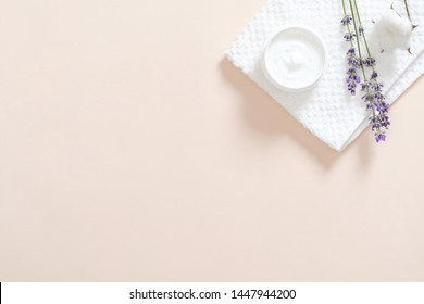 Jar with moisturizing body cream, bath towel, lavender flower, cotton on pastel pink background. Skin care cosmetic concept. Minimal flat lay style composition, top view, copy space.