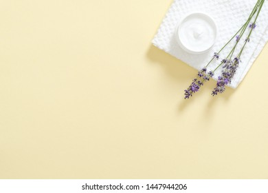 Jar with moisturizing body cream, bath towel, lavender flower on pastel yellow background. Skin care cosmetic concept. Minimal flat lay style composition, top view, copy space.