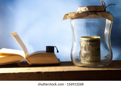 Jar with money, college graduation cap and open book.