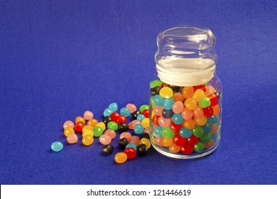 Jar of multicolored Jelly Beans over blue bacground.