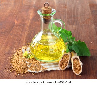 Jar of mustard oil and seeds with mustard flower on wooden background