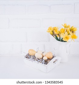 Jar with narcissuses and eggs at the white brick background. Spring and Easter concept. Square