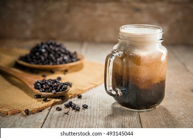Jar of nitro coffee fresh pour from tap rustic lifestyle espresso mocha beans