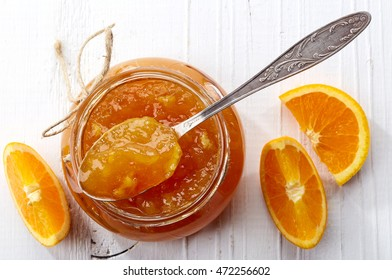 Jar of orange jam on white wooden background from top view