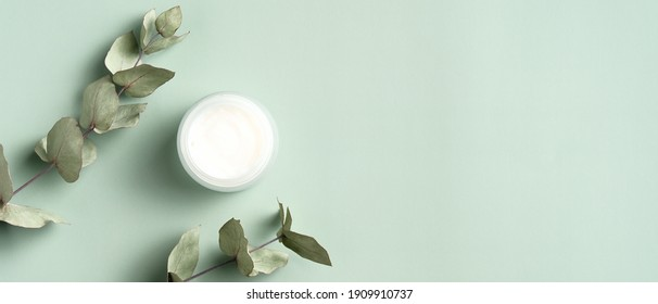 Jar of organic cream with eucalyptus leaves on green background. Flat lay, top view, copy space. Natural organic product, beauty and spa concept