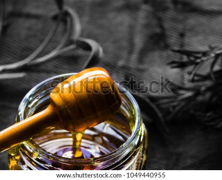 Jar of organic honey and wooden dripper and textured background in mono