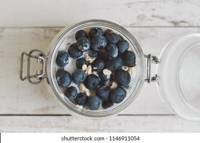 Jar with overnight oats with fresh blueberry. Healthy yougurt with coconut milk and fruits, top view