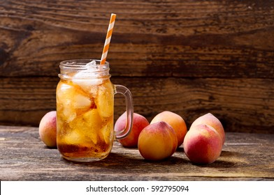 jar of peach iced tea with fresh fruits on a wooden table