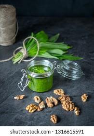 Jar of pesto made from bear garlic with walnuts on gray table.