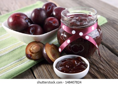 jar of plum jam and some fresh plums