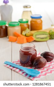 Jar of plum puree and spoon on wooden table. Homemade baby food, natural ingredients and high amount of vitamins.