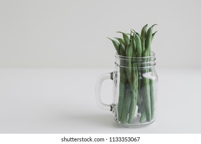 Jar with raw green beans on white table. Minimal food style photo