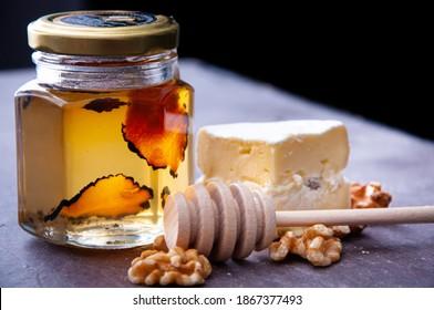 Weihrauch von Rohhonig, der mit Trüffel infundiert wurde. Eine köstliche Begleitung zum Frühstück oder Snack, serviert mit Brie-Käse und mit Walnüssen garniert.
