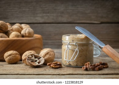 Jar of raw organic walnut butter and fresh nuts on table. Copy space for text.