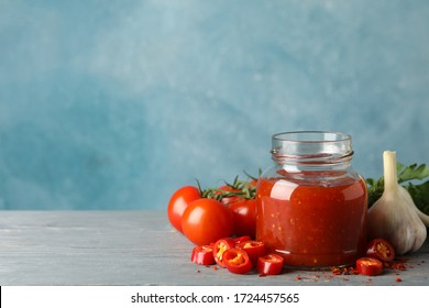 Jar with red chilli and tomato sauce, and spices on wooden table - Shutterstock ID 1724457565