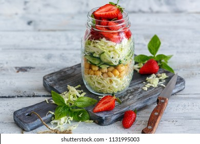 Jar with salad from young cabbage, chickpeas and strawberries with basil on white wooden table.