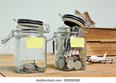 Jar for savings full of coins on wood.