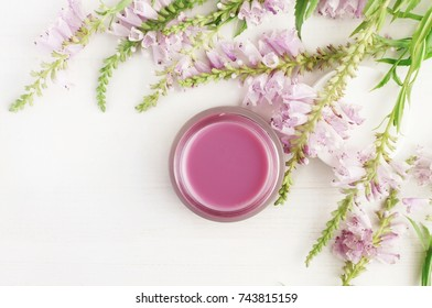 Jar of skin and body care cream framed fresh violet flowers top view white surface, light delicate faded tones