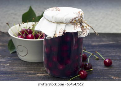 Jar with sour cherry compote on the wooden table