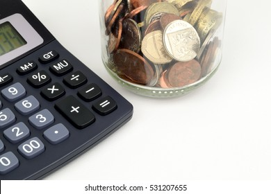A jar of Sterling coins and a calculator to represent Sterling finance.