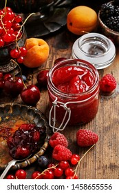 Jar of strawberry jam among summer and autumn fruits on a wooden table.