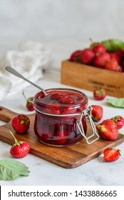 A jar of strawberry jam on a wooden board. Close up