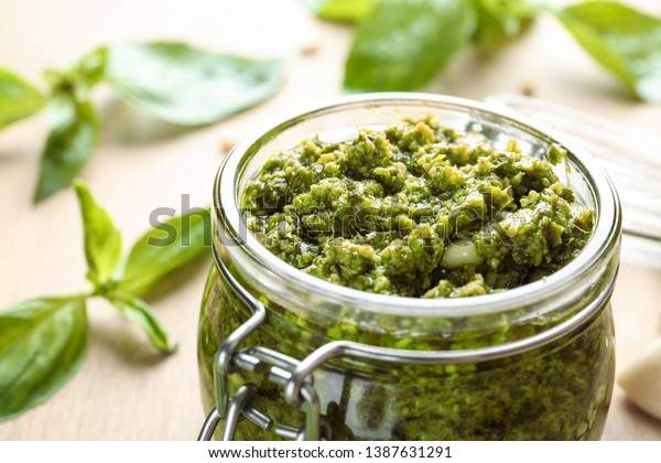 Jar of tasty pesto sauce on table, closeup. Space for text